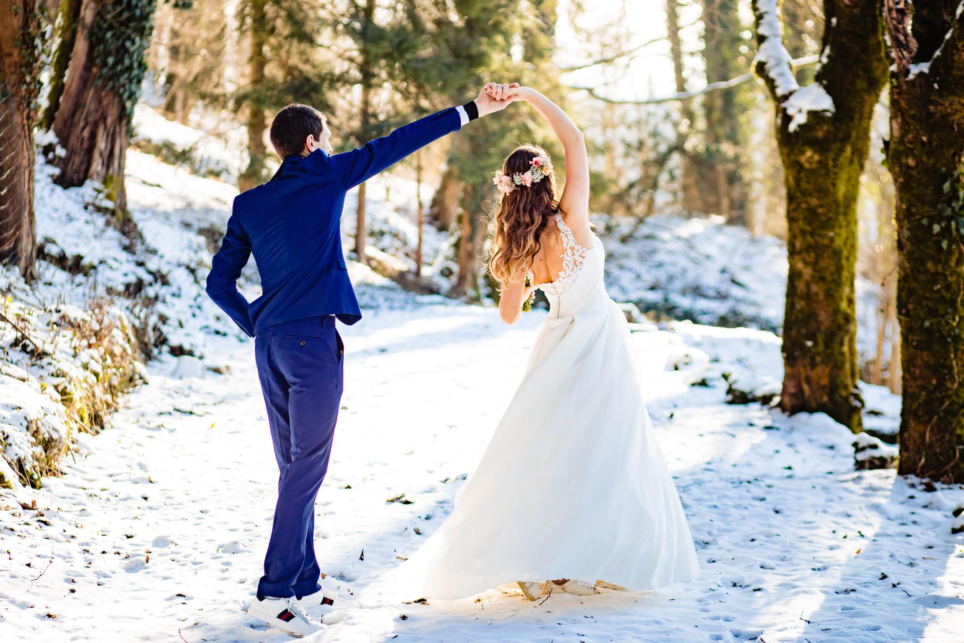 Jeunes mariés dansant dans un jardin enneigé